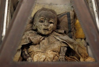 Fully clothed human remains of a child, representing some of the world's best-preserved bodies, are displayed at the Capuchin Catacombs in Palermo, southern Italy, January 31, 2011. The catacombs, frequented by tourists, contain thousands of remains of clerics, nobility, and families of local citizens dating from about the mid-16th century, well preserved due to an ancient and highly effective embalming process. Originally intended for friars of the Capuchin monastery, the catacombs evolved, with the aid of donations, into a place where family members would visit, spend time with and even change the clothes of the deceased. The last burial was Rosalia Lombardo, two-years old, in the 1920s. REUTERS/Tony Gentile (ITALY - Tags: SOCIETY)